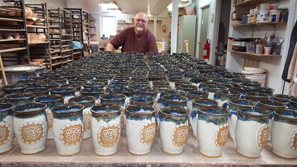 Bob Meier, owner of Doe Ridge Pottery in downtown Boone, stands behind about 200 WNCW mugs.